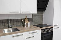 Rechte, witte voorraadkeuken met houtlook werkblad